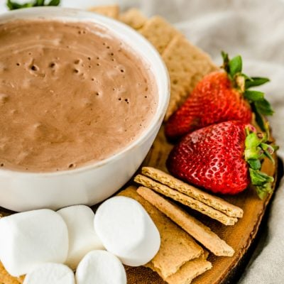 closeup of wooden platter holding s'mores dip and dipping food