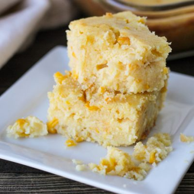 slices of cornbread casserole on a plate with crumbles of bread and corn