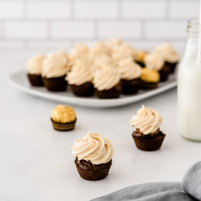 frosted ferrero rocher brownie bite in front of platter full of brownies and jar of milk