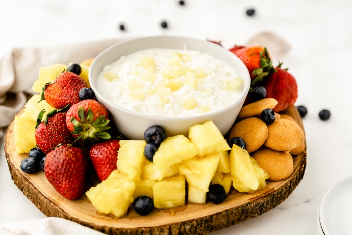 wooden platter with strawberries and pineapple; piña colada fruit dip