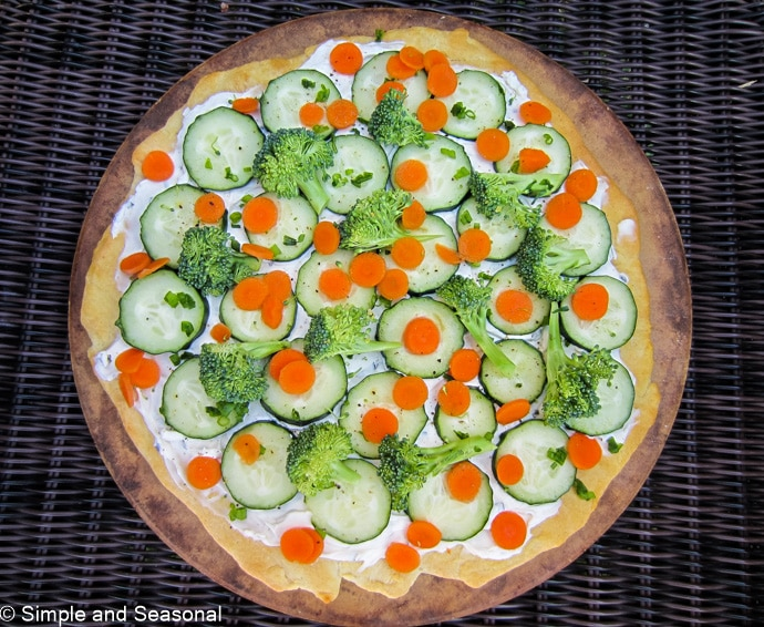 top down view of pizza topped with cream cheese and fresh vegetables