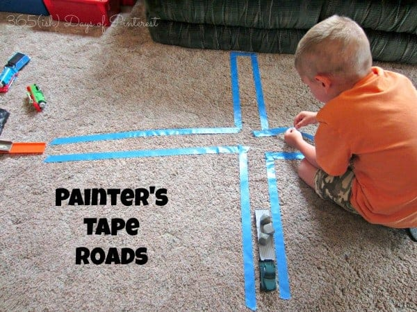 young boy placing blue painters tape on the carpet to make roads