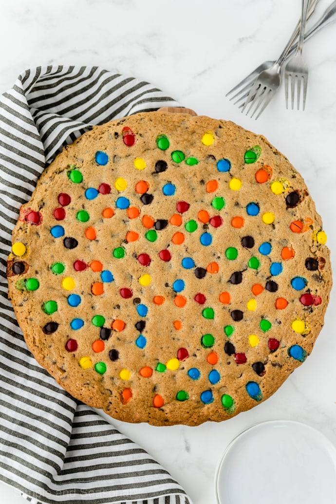 baked, golden brown giant cookie cake with striped kitchen towel in background