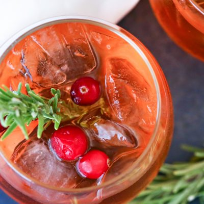 top down view of cranberry punch garnished with fresh berries and rosemary sprigs