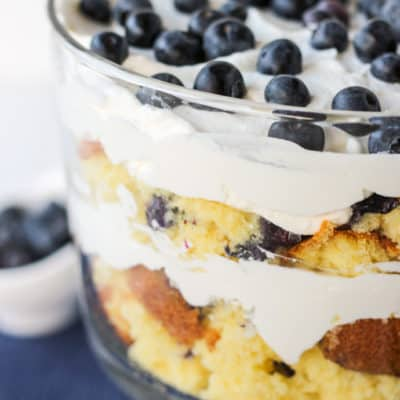 blueberry lemon trifle in a bowl with blueberries in the background