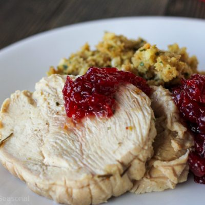 plate of Thanksgiving food: turkey breast slice, cranberry sauce and stuffing