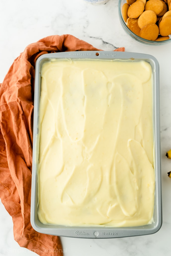 banana pudding poke cake covered in layer of whipped topping
