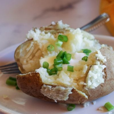 cooked potato on plate with sour cream and butter