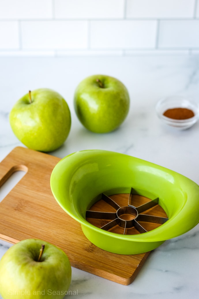 apple cutting tool on a wooden cutting board with green apples