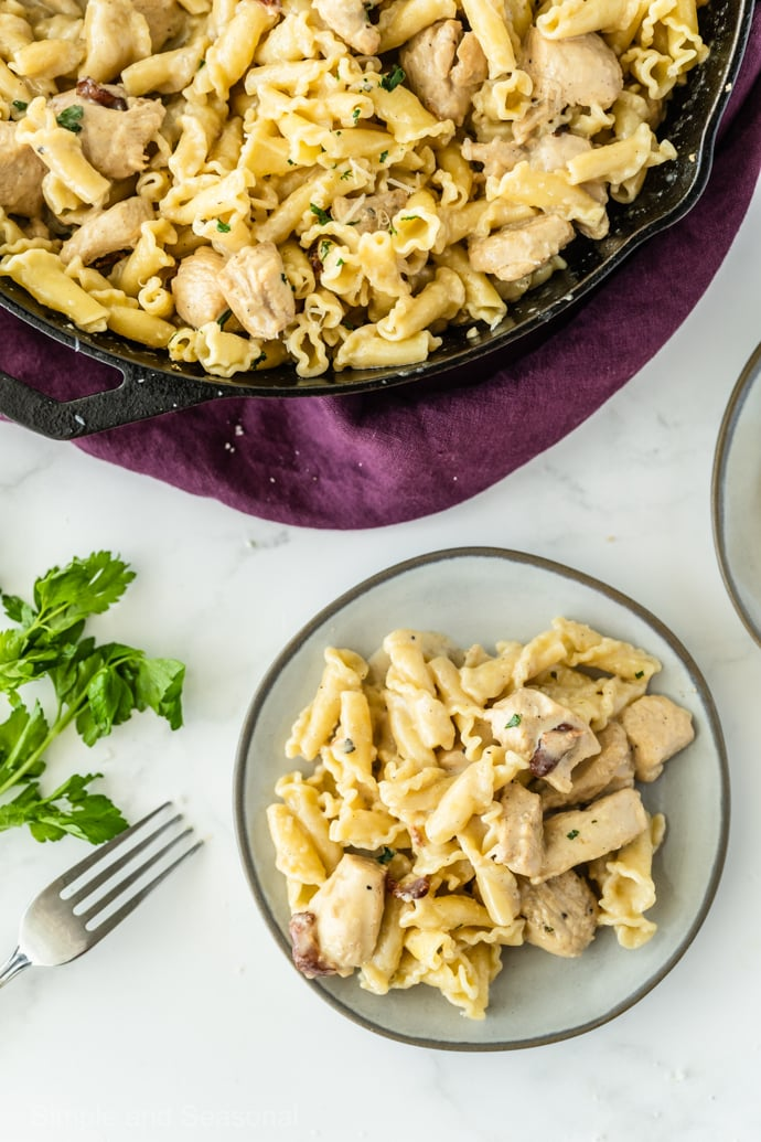plate of chicken bacon pasta with skillet in the background