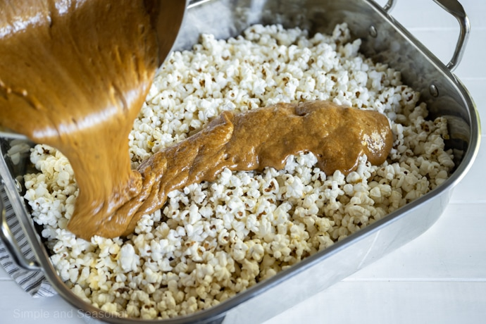 caramel mixture being poured over popped corn