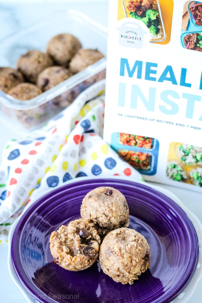 banana oatmeal bites on a plate with a cookbook standing in the background: Meal Prep in an Instant