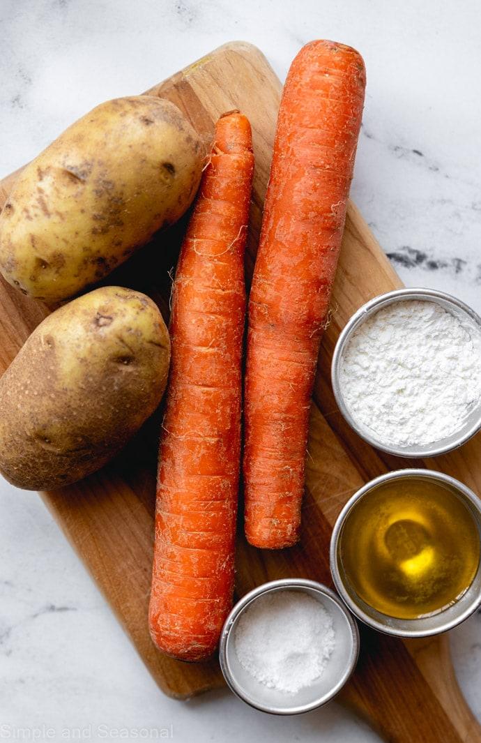raw carrots, potatoes, oil, salt and cornstarch on a cutting board