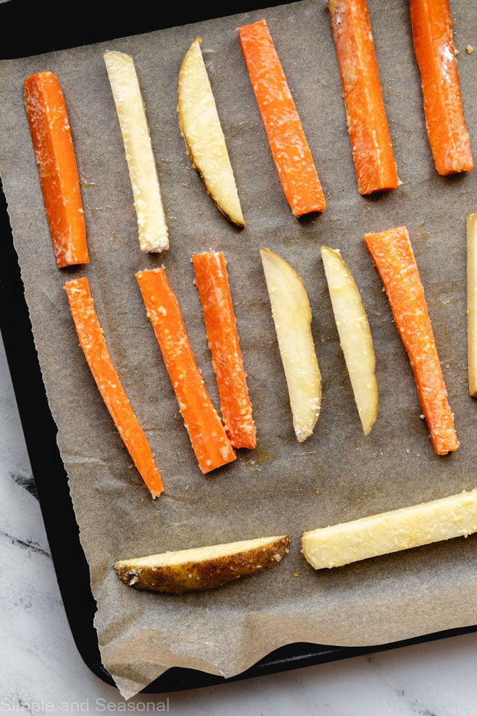 raw carrots and potatoes on parchment lined baking sheet