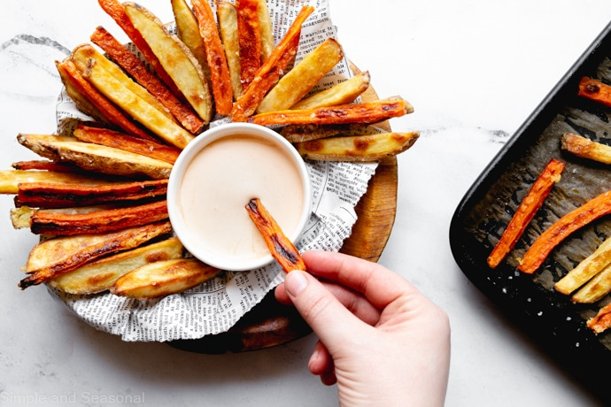 carrot fries and potato fries in a serving bowl, with the baking pan in the background