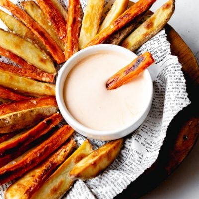 serving tray full of baked carrot fries, potato fries and dipping sauce