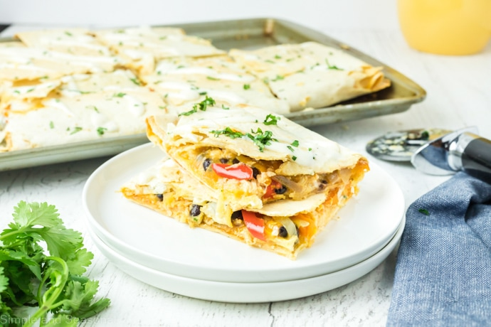 quesadillas pieces on  plate with the sheet pan in the background
